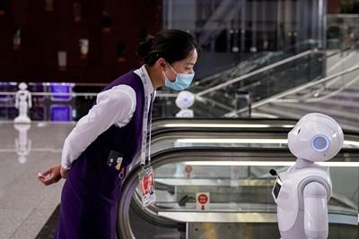 Жена разговаря с робот по време на Световната конференция за изкуствен интелект в Шанхай през 2020 г. СНИМКА: РОЙТЕРС