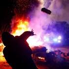 Протестиращ хвърля камък по автобус с евакуирани в Украйна.