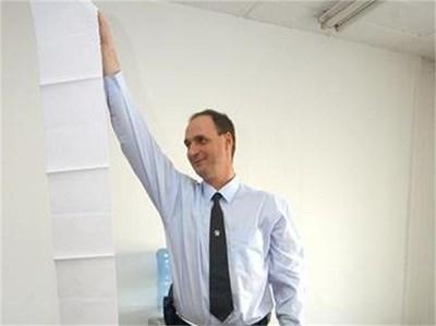 Началникът на Първи сектор в КАТ - София, Иво Кирилов показва 4-метровия списък с нарушенията на рецидивиста Георги.  СНИМКА: ГЕРГАНА ВУТОВА