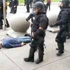 Полицаи подминават възрастен мъж, когото са повалили и главата му кърви.