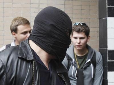 Маскиран московски полицай влиза в блока, където живее блогърът Алексей Навални. СНИМКА: РОЙТЕРС