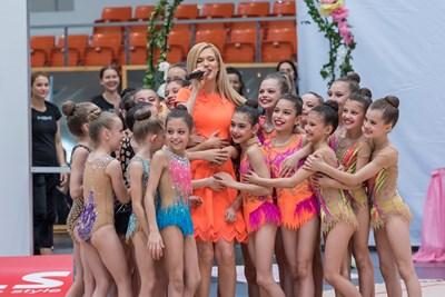 Нели Петкова пее, докато получава прегръдка от част от най-малките гимнастички.