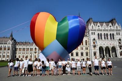 Активисти се събират пред огромен балон с цветовете на дъгата, поставен пред унгарския парламент в  Будапеща в знак на протест срещу анти-ЛГБТ закона.