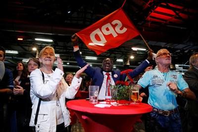 Членове на Социалдемократическата партия празнуват след обявяването на прогнозните резултати.