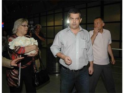 Д-р Атанас Кръстев минути след като кацна на софийското летище в събота вечерта. Вляво от него е майка му с новородената внучка на ръце.  СНИМКА: НИКОЛАЙ ЛИТОВ