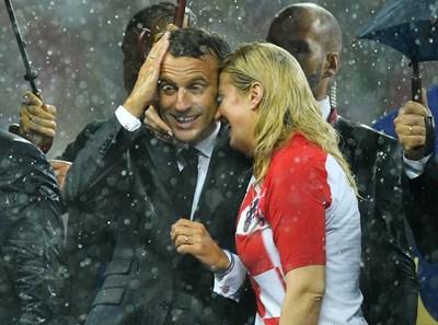 Президентката на Хърватия Колинда Грабар-Китарович прегръща държавния глава на Франция Еманюел Микрон под московския дъжд. СНИМКА: РОЙТЕРС