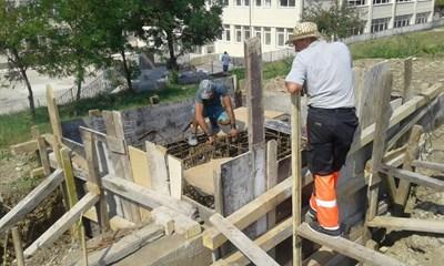 Работници подготвят отливането на фундаментите на стълбовете за осветление