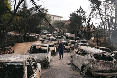 Пожарникар оглежда  стотиците  опожартени  коли в Мати. СНИМКА: РОЙТЕРС