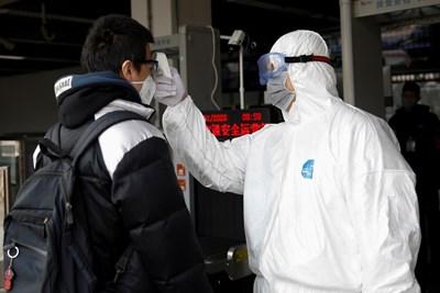 Медицински работник проверява температурата на пътник на летището в град Чанша.