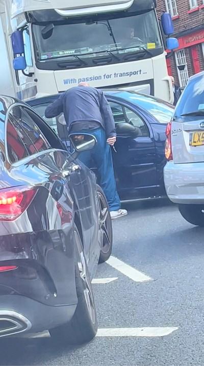 Мъж държи нож и крещи по шофьор, който го е прередил на опашка в бензиностанция в Уелинг, Лондон. СНИМКА: РОЙТЕРС