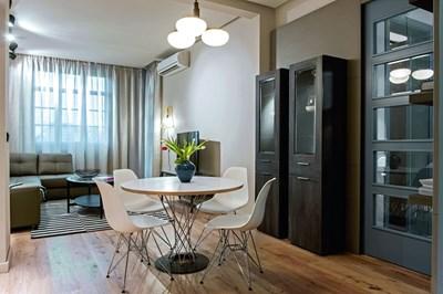 """В трапезарията - маса и столове от """"Хеликс"""". Зад масата за хранене - витрини в неокласически стил, изработени по детайл от """"Ди енд Ди"""". От тавана се спуска запазеният стар полилей"""