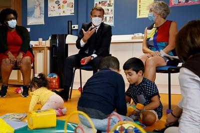 Френският президент Емануел Макрон със задължителната във Франция маска по време на посещение в център за защита на майки и деца край Париж.