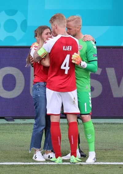 Капитанът на Дания Симон Кяер и вратарят Каспер Шмайхел опитват да успокоят и да дадат кураж на жената на Ериксен Сабрина Квист Йенсен на стадиона. СНИМКА: РОЙТЕРС