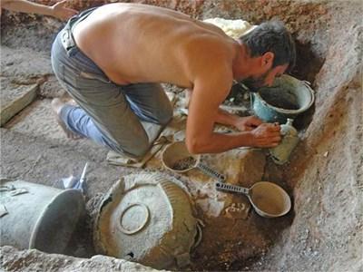 Археологът Деян Дичев почиства луксозните бронзови съдове. На преден план - блюдото и подвижната масичка от комплекта. Вляво - т.нар. шампаниера. СНИМКИ: РУМЯНА ТОНЕВА