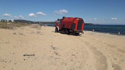 Червеният кемпер е затънал в пясъците по средата на плажа.
