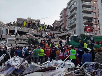 Спасители и жители на Измир търсят оцелели в руините на срината от труса сграда.