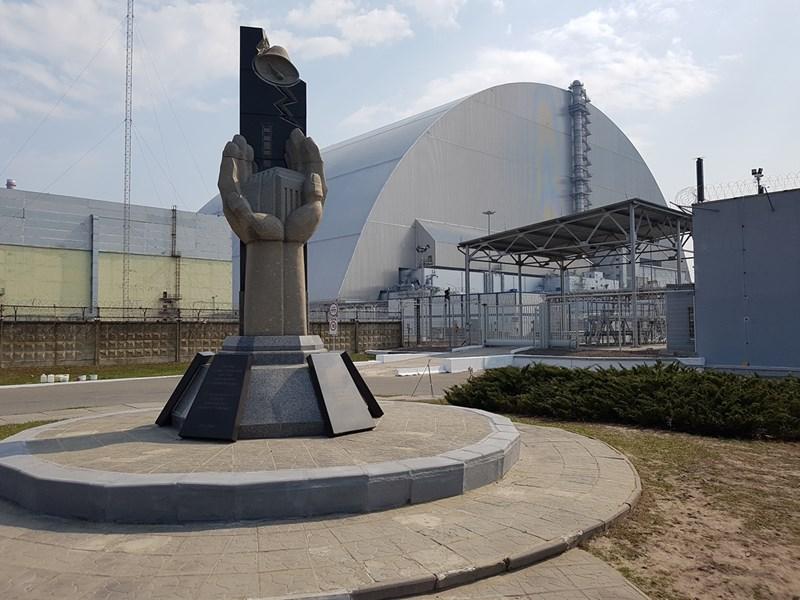 """Паметникът на жертвите, загинали заради """"Чернобил"""". Вдясно е четвърти реактор, покрит със саркофаг."""