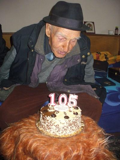 Дядо Стойчо духна днес от раз свещичките върху празничната торта с числото 105.    СНИМКА: Ваньо Стоилов