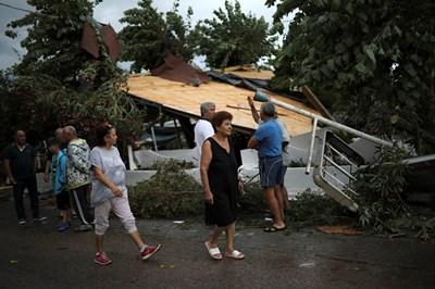Туристи оглеждат щетите след бурята в Гърция.