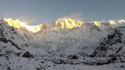 Поглед към Анапурна,  блести златно, огрян от слънцето след прясно нападалия сняг през нощта. 8-хилядникът е по средата на снимката. Хората вдясно изглеждат като мравки на този фон.
