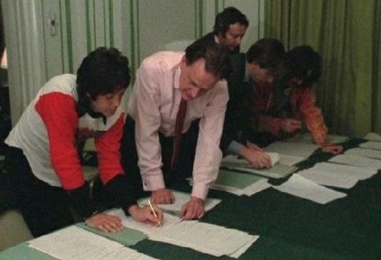 Пол Маккартни подписва споразумението за прекратяване на партьорството. В дъното се вижда и Джордж Харисън.