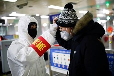 Служител в метрото на Пекин мери температурата на пътник, за да се предотврати плъзването на заразата с коронавируса.  СНИМКИ: РОЙТЕРС