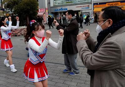 Момичета развеселяват омърлушените жители пред гара в столицата Токио.
