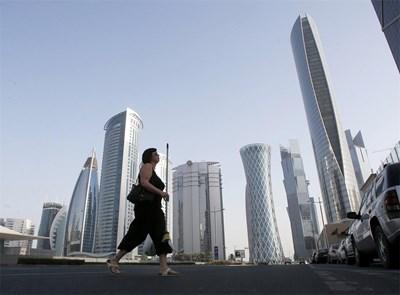 """Жена пресича улица """"Ал Вахда"""" в столицата на Катар Доха. Там  са разположени супермодерни небостъргачи за милиони долари, в които се помещават офисите на богати  компании и банки. СНИМКА: РОЙТЕРС"""