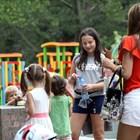 Деца се забавляват в парка в топлото време.