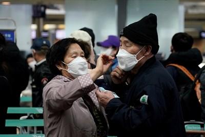 Възрастни южнокорейци си оправят маските на летището в град Инчон.