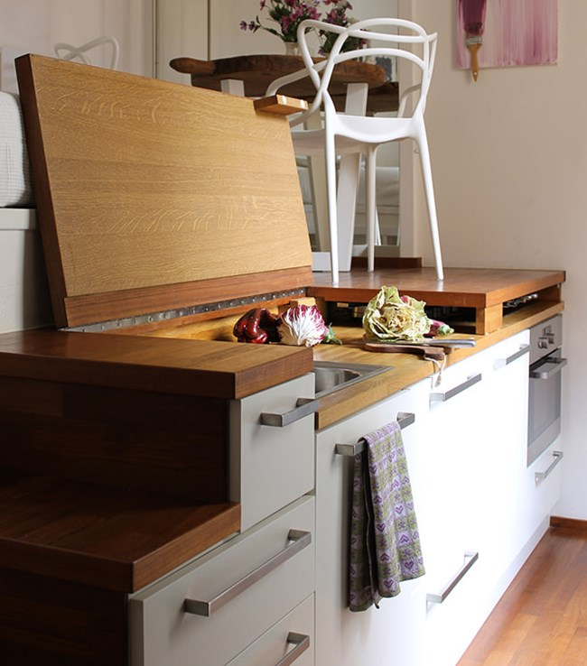 Масичката е точно над кухнята, чиято работна зона се крие под дървени капаци Снимки design-homes.ru