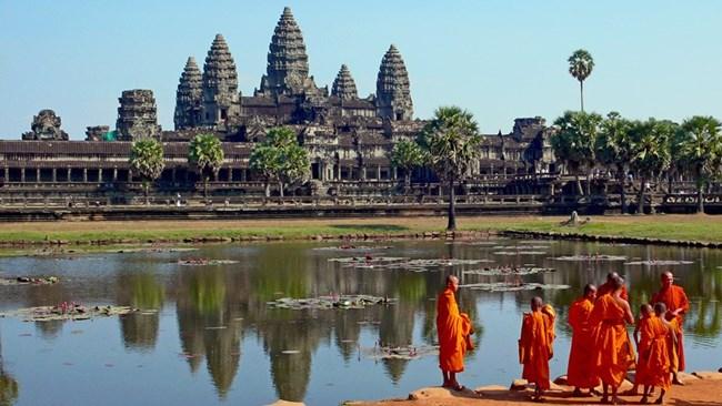Будистки монаси си почиват пред известния храмов комплекс Ангкор Ват в Камбоджа.