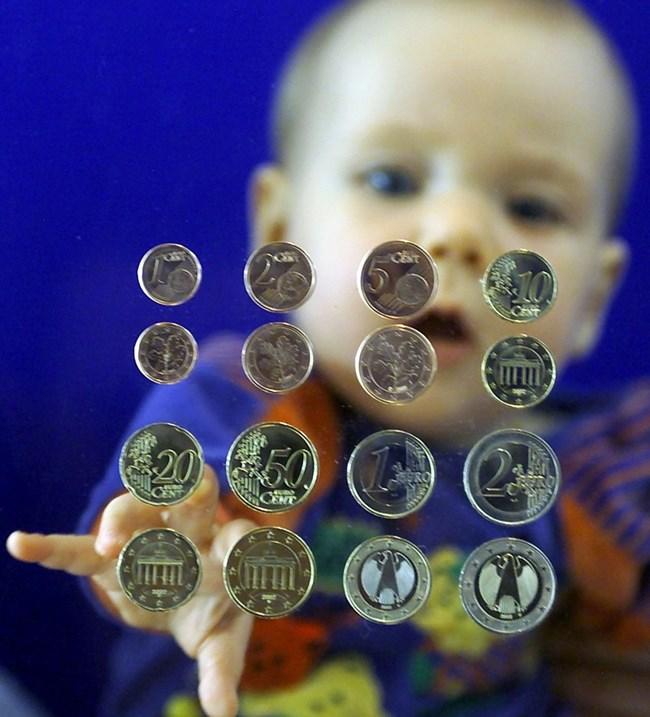Бебе протяга ръка към мостри на евромонетите. В много от тях има никел - най-силният контактен алерген.