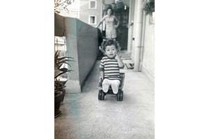 Момченцето с детска количка пред дома си