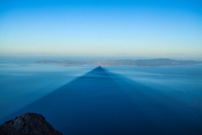 Майсторството на Йордан Симеонов личи и на тази снимка - уловил е сянката на връх Атон, която пада при изгрев-слънце в залива срещу Света гора, отсреща е Ситония - вторият ръкав на Халкидики.
