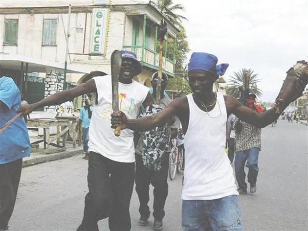 Мъжът най-вдясно носи част от крака на полицай, застрелян, нарязан и изгорен от тълпата заедно с колегата си при бунта на о. Гонаив - столица на наркотрафика в Хаити, на 7 февруари 2004 г.