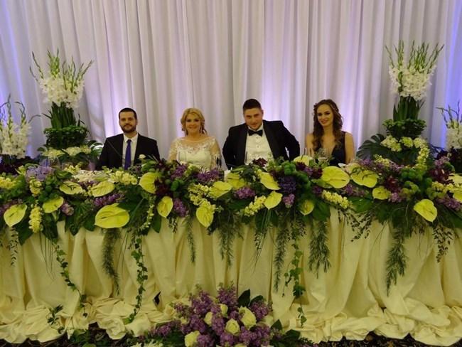 Ева, Стефан и кумовете им на сватбената маса, отрупана с лилави и бели цветя.