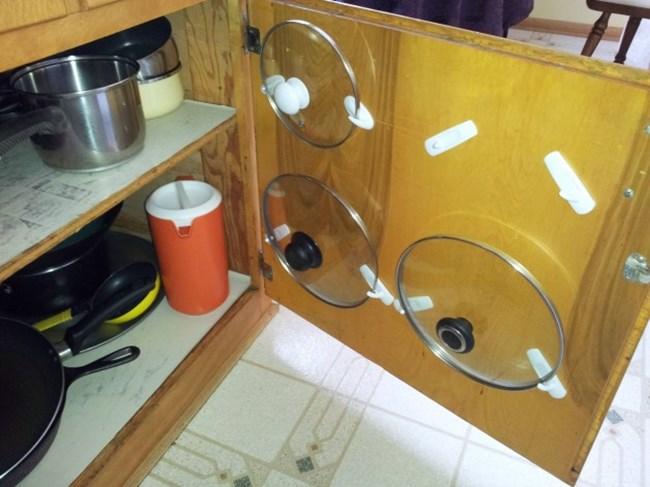Понякога трудно намираме място за капаците на тенджерите. Защо тогава не ги поставим от вътрешната страна на вратата на кухненски шкаф?