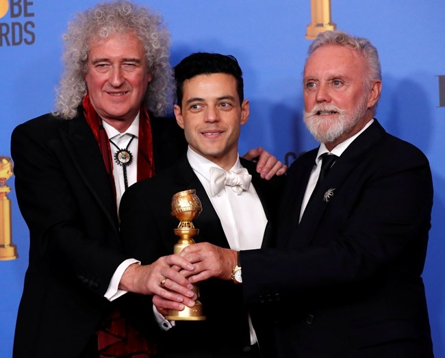 """Рами се радва на наградата си """"Златен глобус"""" в компанията на членовете на """"Куин"""" Брайън Мей и Роджър Тейлър."""
