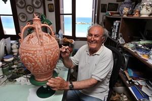 Керамикът Стаматис Фулис от Скирос рисува до прозорец с гледка към Егейско моро