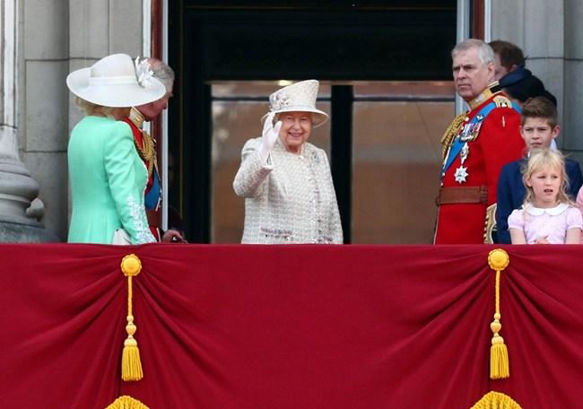 Кралица Елизабет помаха с ръка и се усмихна, когато се появи на балкона, а тълпата я аплодира.